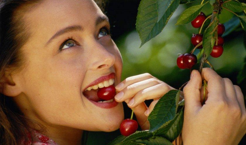Девушка ест вишню
