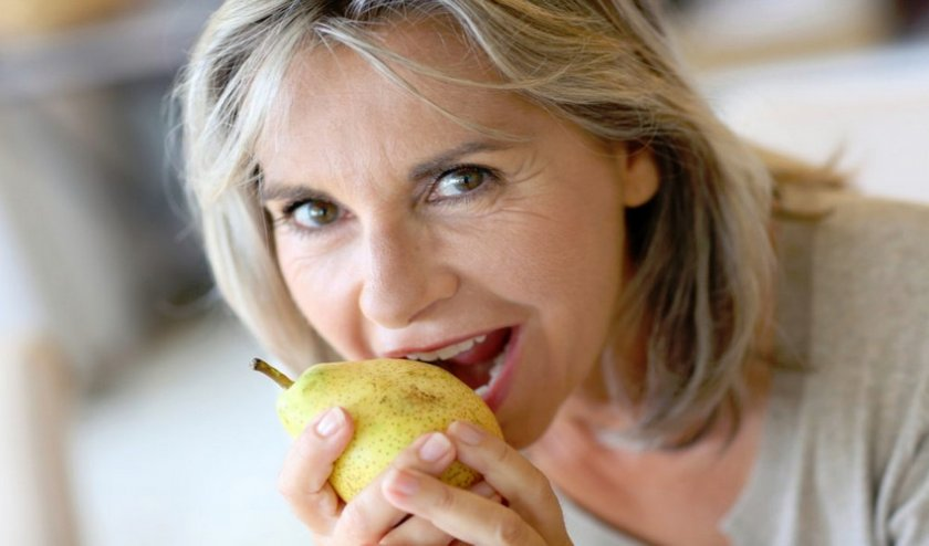 Женщина кушает грушу