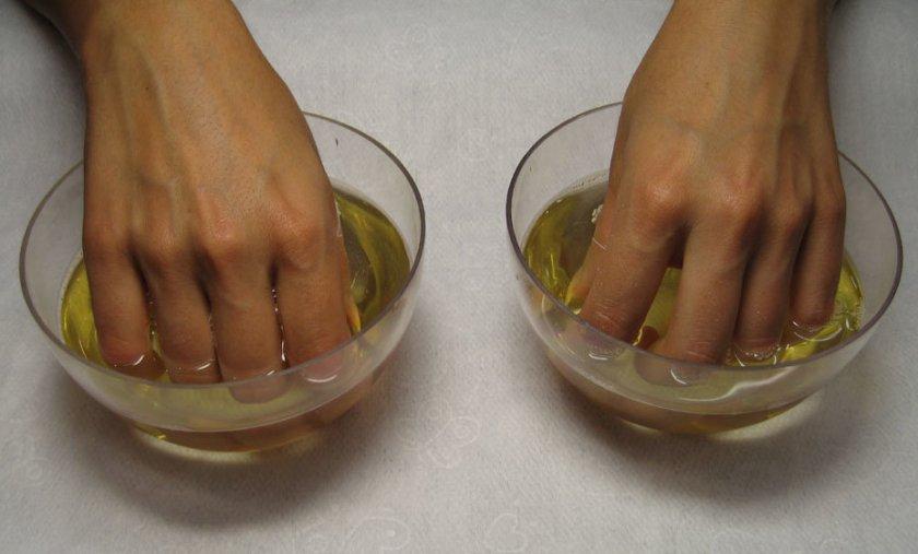 Погружение рук в раствор с абрикосовых маслом